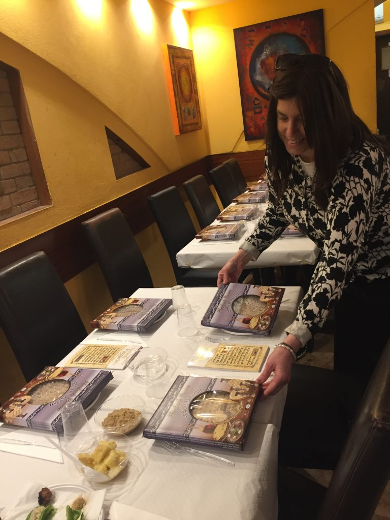 Woman setting the tables for a Passover Seder, including boxes of handmade shmurah matzah.